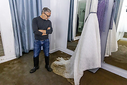 Licensed to London News Pictures. 05/10/2021. London, UK. Fashion designer Jacques Azagury, former dressmaker to Princess Diana, surveys one of his £9,000 silk organza Ivory wedding dress ruined by flood water in his shop in Knightsbridge, west London after torrential rain hit large parts of London last night. Heavy rainfall has caused severe flooding in London with roads blocked with flood water and cars trapped. Photo credit: Alex Lentati/LNP