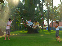 family enjoying their vacation in a resort under the  monsoon rain playing and swing with a hamoc