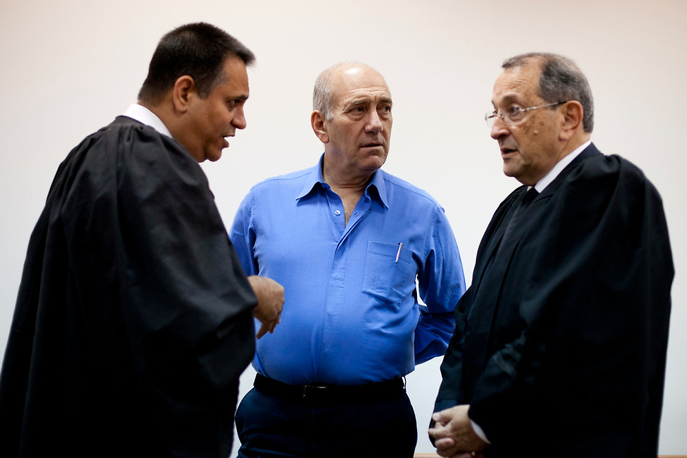 Former Prime Minister of Israel Ehud Olmert (C) is seen at the courtroom of the Jerusalem District Court as his attorney Eli Zohar (R) talks with attorney Micha Pettman who represents Shula Zaken during Olmert's trial, on June 23, 2011.