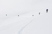 Backcountry skiers skin up a snow slope towards Little Diamond Head, Garibaldi Provincial Park, British Columbia, Canada.