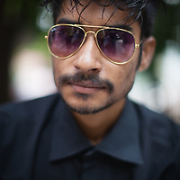 A portrait of a young man in black and with sunglasses in Dhaka, Bangladesh
