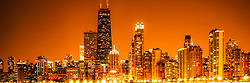 Chicago panorama skyline at night with orange tone. Includes Chicago downtown city buildings and the famous John Hancock Center building. The John Hancock Center is one of the world's tallest skyscrapers and is a popular fixture in the Chicago skyline. Photo panoramic ratio is 1:3 and has an orange tone.