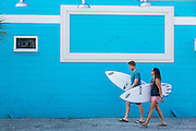 Two young surfers walk past a blue wall in Folly Beach, SC.
