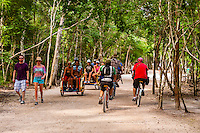 Tourists riding in pedicabs and on bicycles, Coba archaeological site, Riviera Maya, Quintana Roo, Mexico