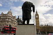 Statue of wartime ex-Prime Minister and statesman, Winston Randolph Churchill on Parliament Square in Westminster, central London. As a Routemaster London bus passes-by, we see the tall artwork that dominates this part of the square. Churchill stoops as an old man, relying on his walking stick and higher in perspective than the tall height of Elizabeth Tower where the bell known as Big Ben is housed, the Gothic architecture of Victoria architect Pugin's building, the seat of parliamentary government in the UK.