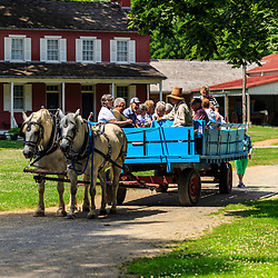 Lancaster, PA – July 12, 2016: Visitors ride in a horse-drawn farm wagon at the Landis Valley Village & Farm Museum in Lancaster County.