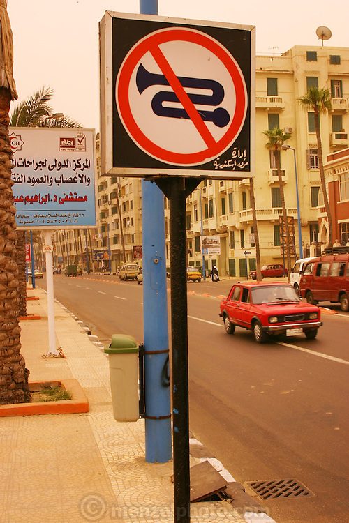 """A """"no-honking"""" sign in downtown Alexandria, Egypt during a sandstorm. The yellow-orange light is from the sand in the sky filtering the sunlight."""