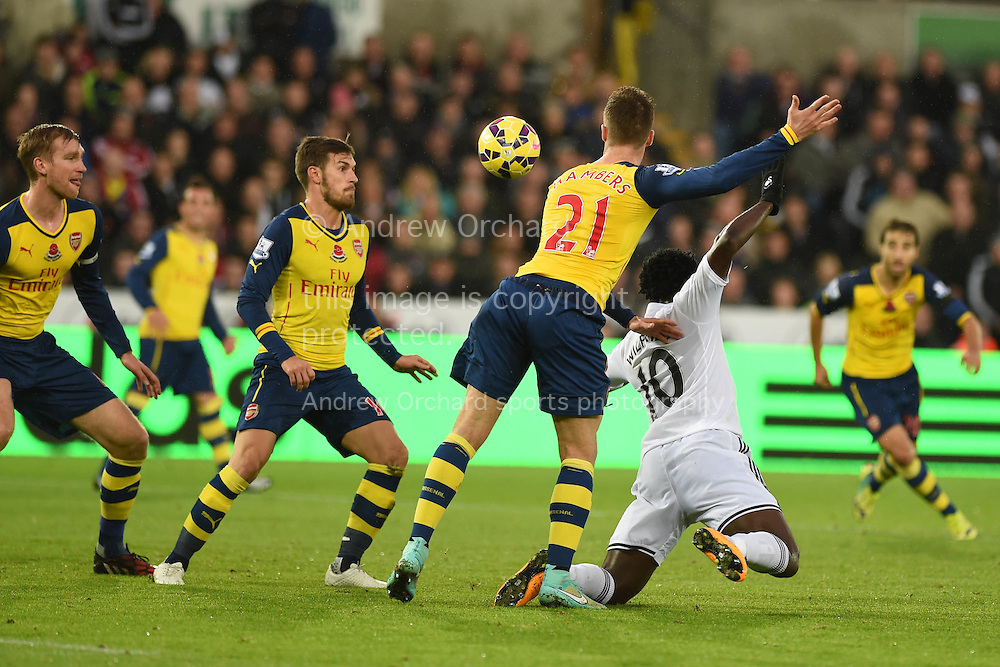 Swansea city's Wilfried Bony (10) appears to get pushed in the penalty area by Arsenal's Calum Chambers (21) but no penalty is given. Barclays Premier league match, Swansea city v Arsenal at the Liberty Stadium in Swansea,  South Wales on Sunday 9th November 2014. <br /> pic by Andrew Orchard, Andrew Orchard sports photography.