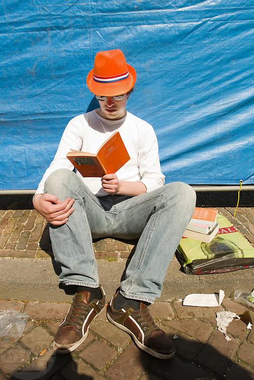 Een jongen leest in het boek 'Majesteit' van Youp van 't Hek op de vrijmarkt in Utrecht tijdens Koninginnedag 2012.<br /> <br /> A man is reading the book 'Majesty' at the flee market on Queensday in Utrecht.