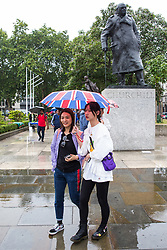 London, UK. 19 July, 2019. Tourists with a Union Jack umbrella brave heavy rain in Parliament Square, Westminster.
