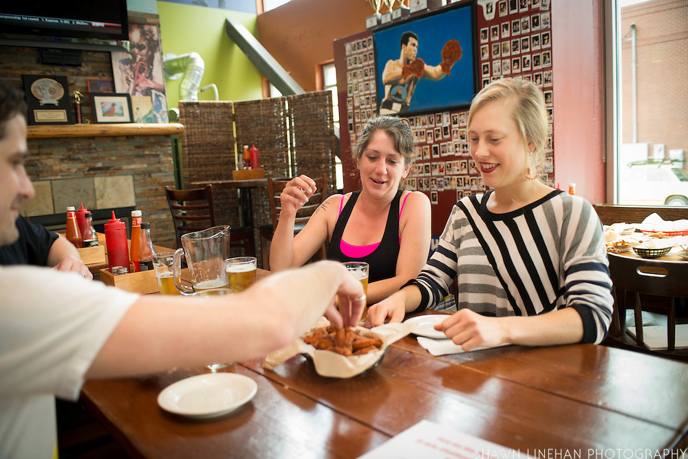 Employees Ranae and Julia try an El Jefe wing.