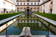 "Alhambra Palace's Patio de Arrayanes (Court of the Myrtles). Patio de los Arrayanes (Court of the Myrtles), also called the Patio de la Alberca (Court of the Blessing or Court of the Pond), from the Arabic birka, ""pool"". The birka helped to cool the palace and acted as a symbol of power. Because water was usually in short supply, the technology required to keep these pools full was expensive and difficult. The court is 42 m (140 ft) long by 22 m (74 ft) broad, and in the centre there is a large pond set in the marble pavement, full of goldfish. Alhambra (in Arabic, Al-Ḥamra) is a palace and fortress complex constructed during the mid 14th century by the Moorish rulers of the Emirate of Granada in Al-Andalus, occupying the top of the hill of the Assabica on the south-eastern border of the city of Granada in the Autonomous Community of Andalusia."
