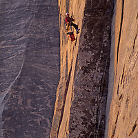 BAFFIN ISLAND, Nunavut, Canada. Alex Lowe, bathed in Arctic midnight sun, rappels from day's high point on upper wall of Great Sail Peak, an extreme northern big-wall rock climb.