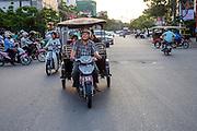Een tuktuk rijdt door Phnom Penh. De tuktuk is een populaire manier van vervoer in de hoofdstad van Cambodja. Het gemotoriseerd vervoer heeft de fiets verdreven/