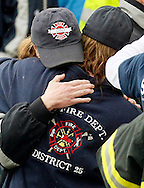 Women hug at the Oso fire station after a moment of silence for those lost in the mudsilde exactly one week ago in Oso, Washington March 29, 2014.  Family and friends of 90 people still missing after a wall of mud flattened the outskirts of a rural Washington state town increasingly feared for the worst on Saturday as the governor called for a statewide moment of silence a week after the disaster. REUTERS/Rick Wilking(UNITED STATES)