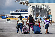 Evacuees walk to an awaiting ferry boat at Marsh Harbour Dock in Abaco on Friday, September 6, 2019.