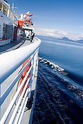 USA, Alaska,A photographer takes in the scenic views from the deck of a Alaska State ferry along the Inside Passage in Southeast Alaska.