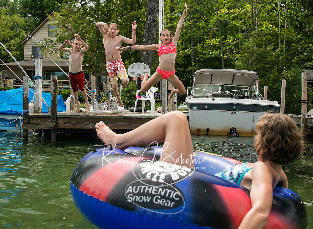 The Kumph family takes the plunge into Lake Winnipesaukee from Varney Point on Tuesday afternoon.  (Karen Bobotas/for the Laconia Daily Sun)