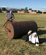 """Humorous photograph of a man pushing a large roller over a nun visually depicting the saying """"Holy roller!"""""""