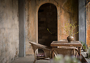 Vase on table, chair and arched door, Pigs Inn, Bishan, Anhui Province, China