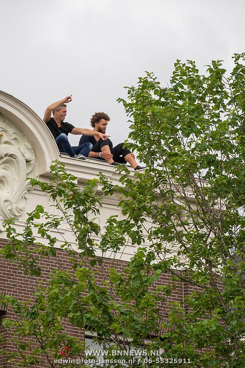 NLD/Amsterdam/20190803 - Gaypride 2019, jongeren op dak van grachtenpand