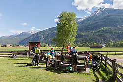 Group of friends preparing for rock climbing, Otztal, Tyrol, Austria