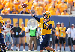Sep 14, 2019; Morgantown, WV, USA; West Virginia Mountaineers quarterback Austin Kendall (12) throws a touchdown pass during the fourth quarter against the North Carolina State Wolfpack at Mountaineer Field at Milan Puskar Stadium. Mandatory Credit: Ben Queen-USA TODAY Sports