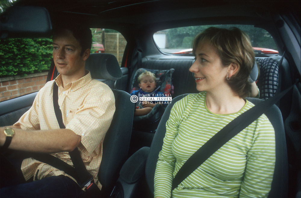 Family sitting in car with father driving and young child strapped into car seat,