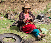 Day 1 of 10 days trekking around Alpamayo: A campesino woman knits in Huaripampa Valley, near Vaqueria, Cordillera Blanca, Andes Mountains, Peru, South America.
