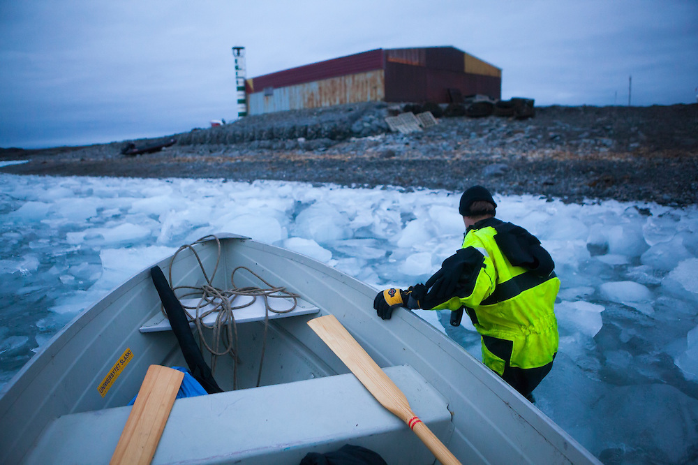 Scientists (Jaroslaw Halat) return late from the field to the ice-choked shore of the Polish Polar Station in Svalbard.