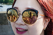 A young lady from South Korea wearing sun glasses which are reflecting the surrounding on Charles Bridge in Prague. The Charles Bridge (Czech: Karlův most) is a famous historic bridge that crosses the Vltava river in Prague, Czech Republic and is probably the Nr.1 tourists magnet in the city.