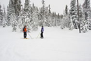 Two young women face each other and talk while on cross country ski's on a snow covered trail in Bend, Oregon. (releasecode: jk_mr1033, jk_mr1032) (Model Released)