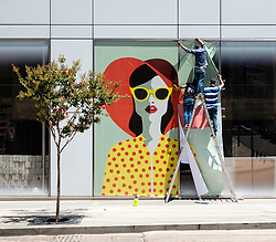 Workers installing colourful mural decoration to new shop in Downtown Beirut, Lebanon