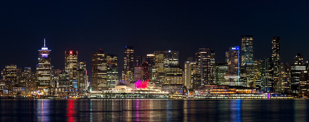 The lights of the city of Vancouver's downtown at sunset. Buildings here include Harbour Center, Canada Place, and the Convention Center.  Photographed from the Burrard Dry Dock Pier (near Londsdale Quay) in North Vancouver, British Columbia Canada across Burrard Inlet from Vancouver.