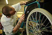 A prisoner rebuilding a wheelchair at the  Inside Out trust workshop.