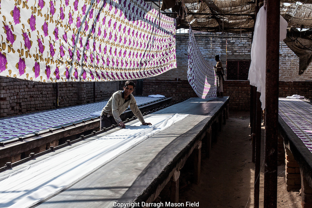 Workers hang printed fabric and place white fabric which is a cotton silk mix.