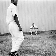 ..Michael Lowe finds solitude with his pocket Bible as the ministry preaches nearby at the Michael Prison near Palestine, Texas.