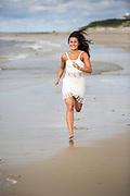 A young woman runs on a beach.