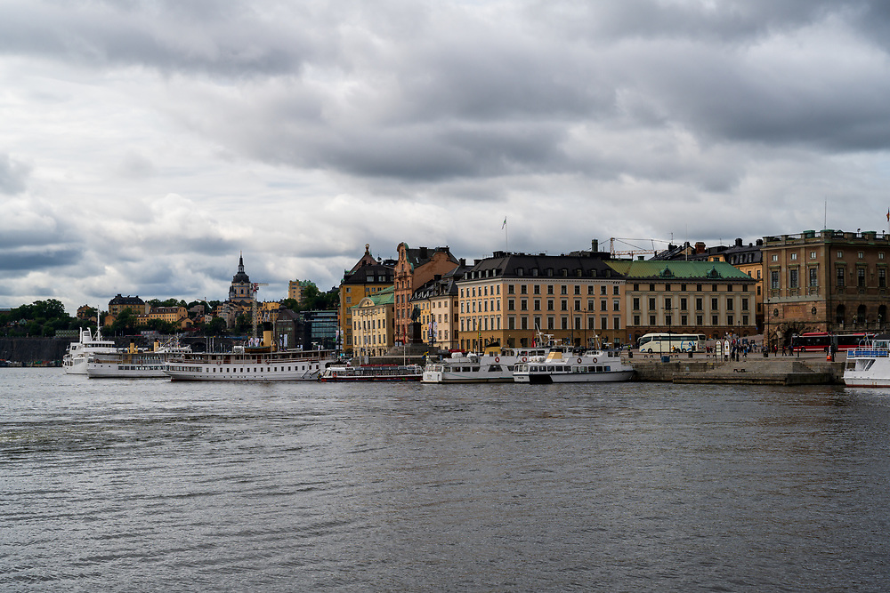 Stockholm, Sweden -- July 16, 2019. On a cloudy day tour boats and ferries are docked in the Royal Canal near large hotels.