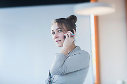 Mature woman talking on mobile phone in lecture hall, Freiburg Im Breisgau, Baden-Württemberg, Germany