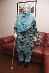Portrait of elderly south Asian woman with stick.