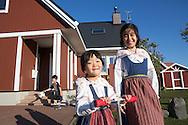 Systrarna Sakura och Haruka Tago och brodern Rintaro utanför familjens faluröda hus i Sweden Hills, Japan.