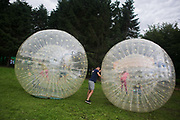 Children play and bounce about in zorb, inflateable giant balls in Scotland 29th of July 2016.