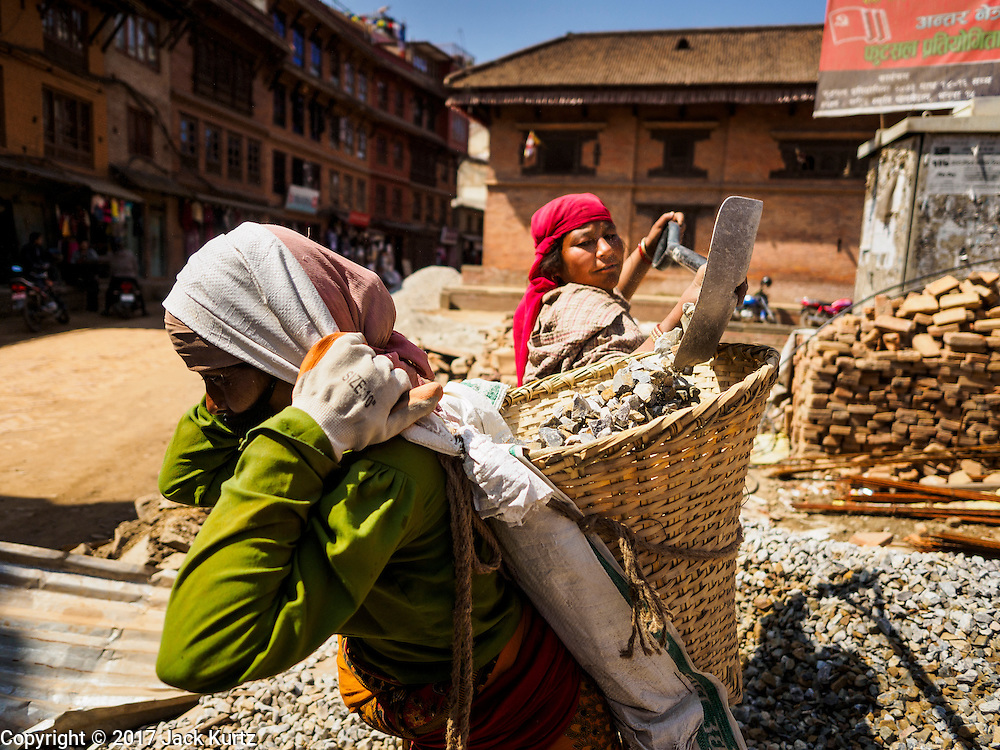 03 MARCH 2017 - BHAKTAPUR, NEPAL: A woman loads another woman's basket with gravel for reconstruction in a historic section of Bhaktapur. Bhaktapur, a popular tourist destination and one of the most historic cities in Nepal was one of the hardest hit cities in the earthquake. Recovery seems to have barely begun nearly two years after the earthquake of 25 April 2015 that devastated Nepal. In some villages in the Kathmandu valley workers are working by hand to remove ruble and dig out destroyed buildings. About 9,000 people were killed and another 22,000 injured by the earthquake. The epicenter of the earthquake was east of the Gorka district.      PHOTO BY JACK KURTZ