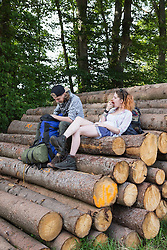 Young couple resting on woodpile in a forest, Bavaria, Germany
