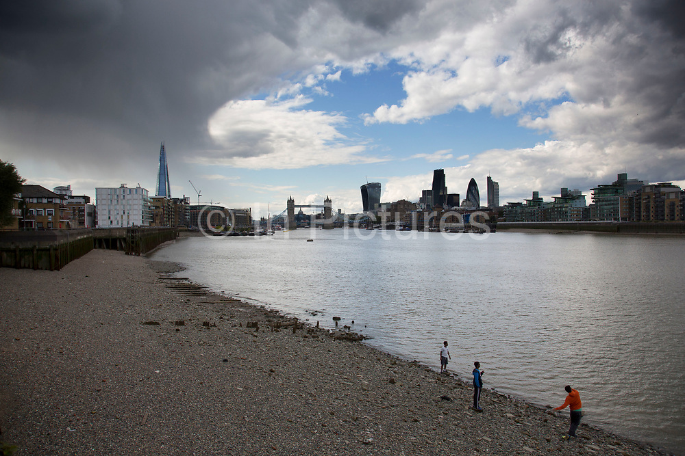 London, UK. Tuesday 19th August 2014. A rain shower falls over The Shard as the City of London remains dry in the sun under blue sky. Summer 2014 has been a stormy season of two halves with a great deal of sudden rain storms followed by bright sunny weather.