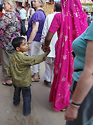 A boy gives a very skeptical look to the foreigners surrounding him; Pushkar, Rajasthan.