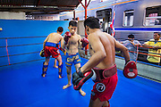 """18 DECEMBER 2104 - BANGKOK, THAILAND: Boxers work out while a commuter train goes by the Kanisorn gym. The Kanisorn boxing gym is a small gym along the Wong Wian Yai - Samut Sakhon train tracks. Young people from the nearby communities come to the gym to learn Thai boxing. Muay Thai (Muai Thai) is a Thai fighting sport that uses stand-up striking along with various clinching techniques. It is sometimes known as """"the art of eight limbs"""" because it is characterized by the combined use of fists, elbows, knees, shins, being associated with a good physical preparation that makes a full-contact fighter very efficient. Muay Thai became widespread internationally in the twentieth century, when practitioners defeated notable practitioners of other martial arts. A professional league is governed by the World Muay Thai Council. Muay Thai is frequently seen as a way out of poverty for young Thais and Muay Thai camps and schools are frequently crowded. Muay Thai professionals and champions are often celebrities in Thailand.     PHOTO BY JACK KURTZ"""