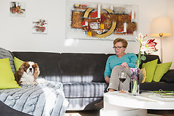 Woman relaxing with Cavalier king charles spaniel dog on sofa
