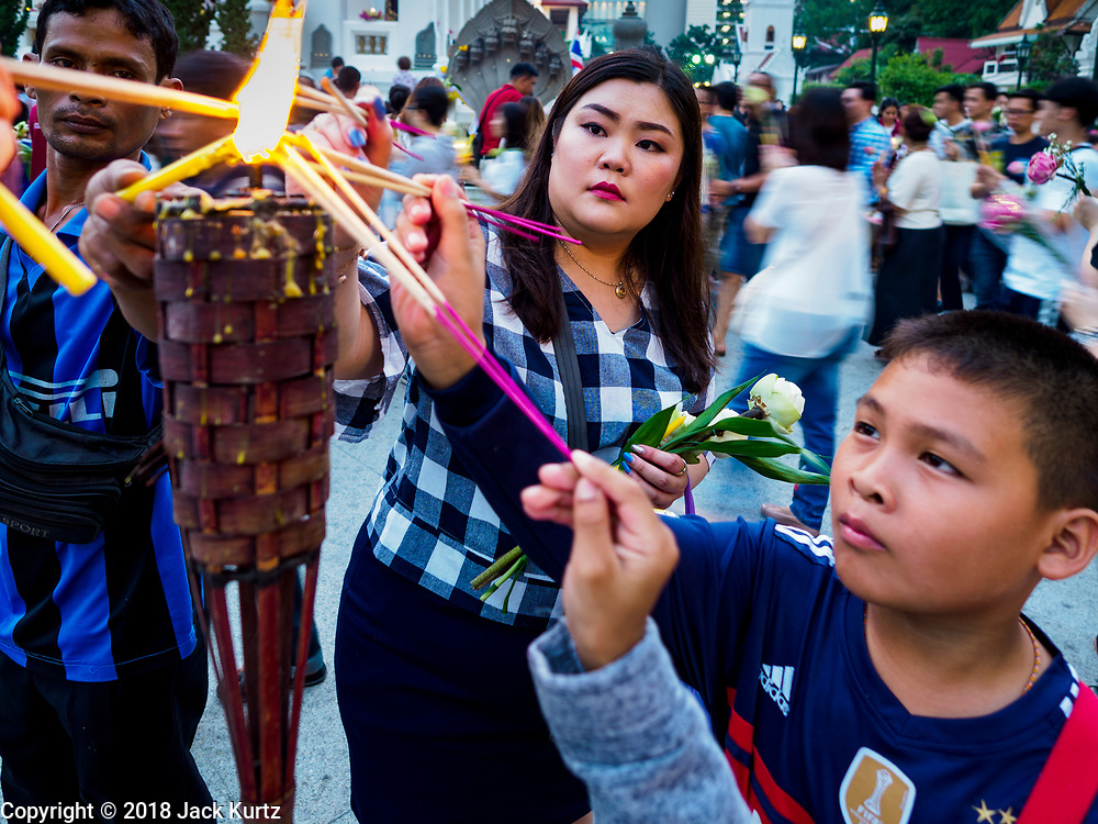 """01 MARCH 2018 - BANGKOK, THAILAND:    People light prayer candles before joining a procession around Wat Pathum Wanaram in central Bangkok. Many people go to temples to perform merit-making activities on Makha Bucha Day, which marks four important events in Buddhism: 1,250 disciples came to see the Buddha without being summoned, all of them were Arhantas, or Enlightened Ones, and all were ordained by the Buddha himself. The Buddha gave those Arhantas the principles of Buddhism. In Thailand, this teaching has been dubbed the """"Heart of Buddhism.""""    PHOTO BY JACK KURTZ"""
